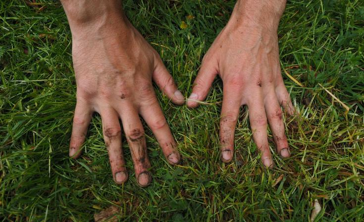 Earth-stained hands pressed firmly against grassy ground