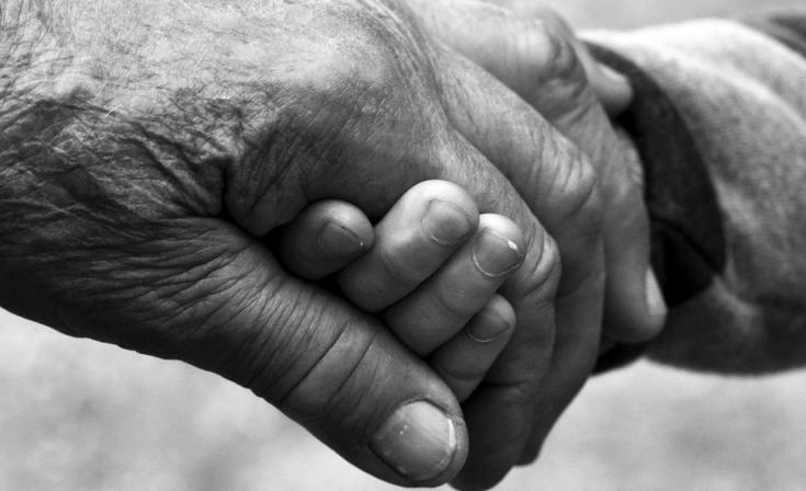 Close up on holding hands - one old and one young hand