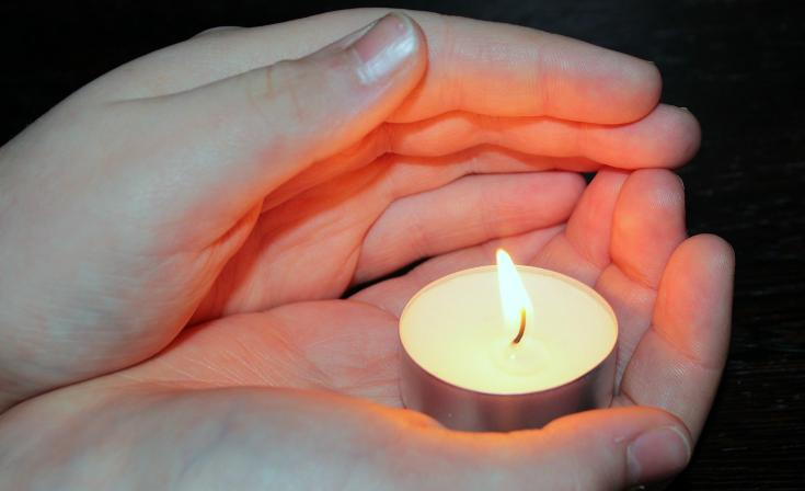 A tealight candle held in the palm of someone's hand as their other hand shelters the flame.