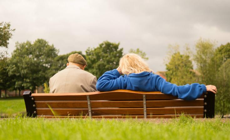 An elderly man and a woman sit on a park bench with their backs to the camera.