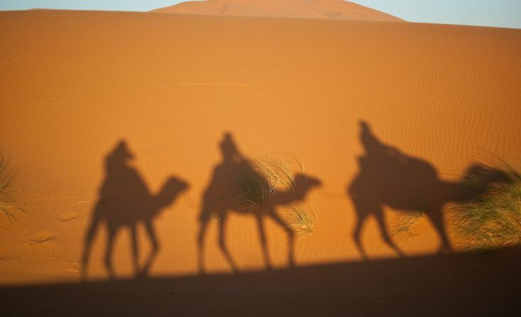 Silhouette of three men on camels