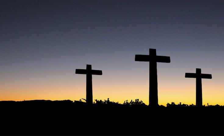 Three crosses silhouetted with a sunset in the background