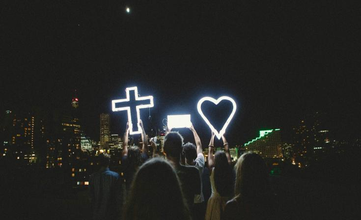 People gathered with an LED light-up cross and heart