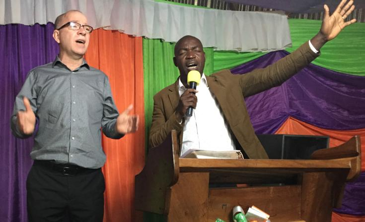 Craig Bailey (left) participates in worship with Ugandan church leaders.
